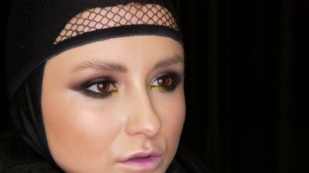 luto : Professional girl model with beautiful makeup poses in a black cap on her head in front of the camera on black background in the image of a black widow. High-fashion Stock Footage