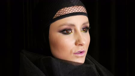 viuda : Professional girl model with beautiful makeup poses in a black cap on her head in front of the camera on black background in the image of a black widow. High-fashion Archivo de Video