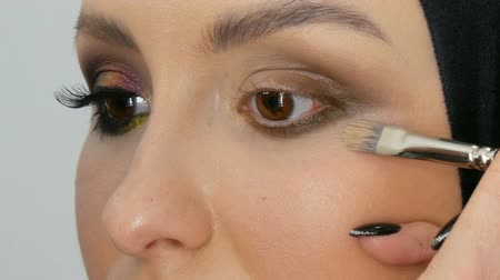 szemgolyó : Professional stylist make-up artist makes eye makeup model. Face model with evening makeup close up view