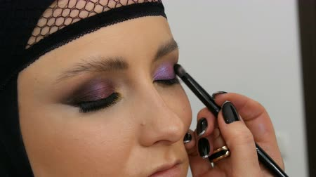 chiarezza : Professional stylist make-up artist makes eye makeup model. Face model with evening makeup close up view