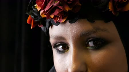viuda : Professional girl model with beautiful makeup poses in a black cap and wreath on her head in front of the camera on black background in the image of a black widow. High-fashion Archivo de Video