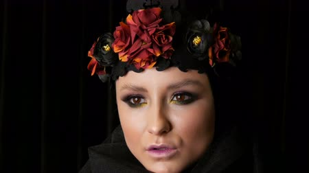 trumna : Professional girl model with beautiful makeup poses in a black cap and wreath on her head in front of the camera on black background in the image of a black widow. High-fashion Wideo