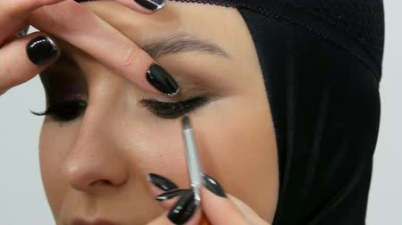 globo ocular : Professional stylist make-up artist makes eye makeup model. Face model with evening makeup close up view