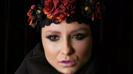 luto : Professional girl model with beautiful makeup poses in a black cap and wreath on her head in front of the camera on black background in the image of a black widow. High-fashion Stock Footage