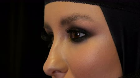 kırmızı şarap : Professional girl model with beautiful makeup poses in a black cap on her head in front of the camera on black background in the image of a black widow. High-fashion Stok Video