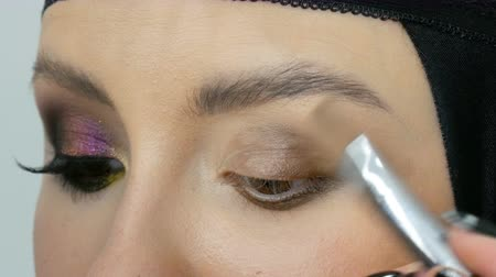 füstös : Professional stylist make-up artist makes eye makeup model. Face model with evening makeup close up view