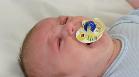 contornos : Two month old newborn baby cries loudly with pacifier in mouth. Child face close up view Vídeos