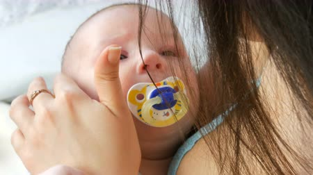 contornos : A beautiful young long-haired mother gently touches and cradles her newborn baby in arms while sitting on her bed. The childs face close up view Vídeos