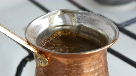 гравюра : Ground black coffee in a copper Turk is brewed and boils on a gas stove. Barista preparing hot tasty drink at home