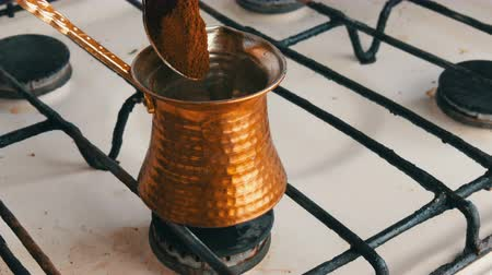 gravure : Teaspoon puts black ground coffee in a copper Turk which stands on white gas stove Stockvideo