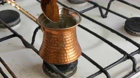 kapasite : Teaspoon puts black ground coffee in a copper Turk which stands on white gas stove Stok Video