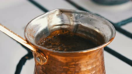 kapasite : Ground black coffee in a copper Turk is brewed and boils on a gas stove. Barista preparing hot tasty drink at home close up