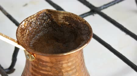 brew coffee : Boiled away runaway ground black coffee in a copper turk on white gas stove