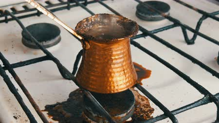 gravure : Boiled away runaway ground black coffee in a copper turk on white gas stove