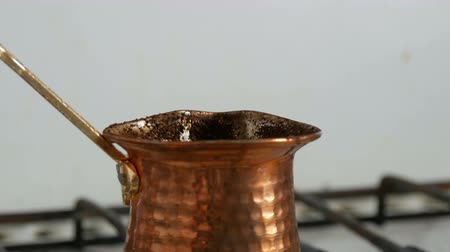 kapasite : Boiled away runaway ground black coffee in a copper turk on white gas stove close up view