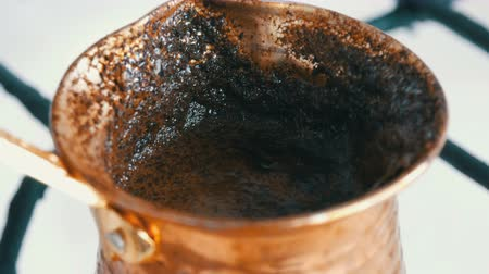 gravura : Boiled away runaway ground black coffee in a copper turk on white gas stove