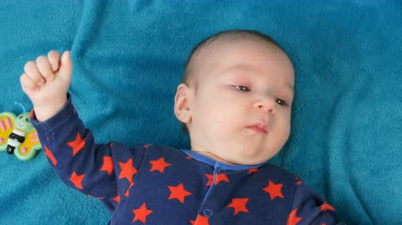contornos : Portrait of beautiful funny little newborn baby of two months lying on a blue bedspread surrounded by baby rattles