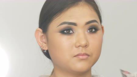 make up artist : Professional make-up artist makes eye makeup of Korean girl Asian woman with special brush