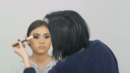 蛍光ペン : Professional makeup artist applies foundation concealer or highlighter to Asian Korean models face with special brush
