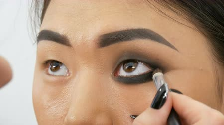 szemgolyó : Professional make-up artist makes eye makeup of Korean girl Asian woman with special brush
