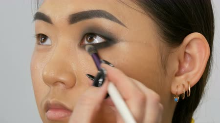 wzrok : Professional make-up artist makes eye makeup of Korean girl Asian woman with special brush