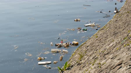 mc : Amsterdam, Netherlands - April 21, 2019: A lot of garbage, plastic bottles and paper float on the embankment river channel of the capital of the Netherlands Amsterdam