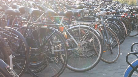 multiculturalità : Amsterdam, Netherlands - April 21, 2019: Parking for bicycles. Many different bicycles parked on a street in special parking lots. The problem of bicycle overload in the country Filmati Stock