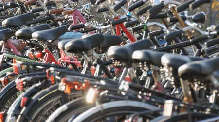 zaparkoval : Amsterdam, Netherlands - April 21, 2019: Parking for bicycles. Many different bicycles parked on a street in special parking lots. The problem of bicycle overload in the country Dostupné videozáznamy