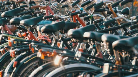 trançado : Amsterdam, Netherlands - April 21, 2019: Parking for bicycles. Many different bicycles parked on a street in special parking lots. The problem of bicycle overload in the country Stock Footage