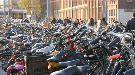 pedestres : Amsterdam, Netherlands - April 21, 2019: Parking for bicycles. Many different bicycles parked on a street in special parking lots. The problem of bicycle overload in the country Stock Footage