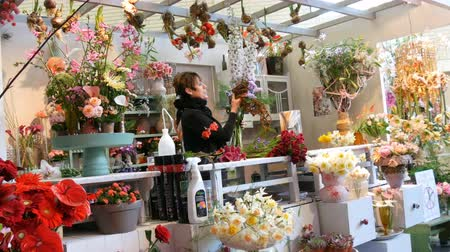 floriculture : Lisse, Netherlands - April 22, 2019: A female florist demonstrates the process of making bouquet of fresh flowers in the royal park Keukenhof