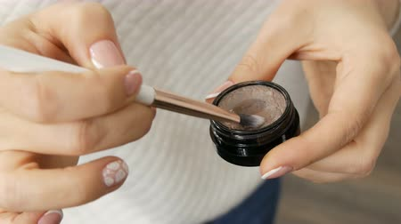 rty : Makeup artist hands mix dried eyeshadow with a special brush in beauty salon