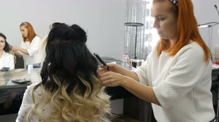 гладильный : Woman Woman hairdresser stylist does a curl of curls of hair in a beauty salon with special curling iron. Long beautiful hair of black and white color of a young woman dyed using ombre technique Стоковые видеозаписи