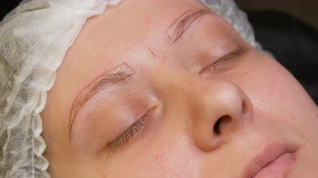 маркировка : A young woman in a cometology room with a microblading powder spraying just made brow correction. Permanent makeup. Tattoo New technologies in cosmetology
