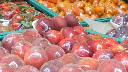 őszibarack : Peaches, Nectarine, apricots, strawberries, kiwi on street market counter under special cellophane cloth, protected from dust and moisture. Stock mozgókép