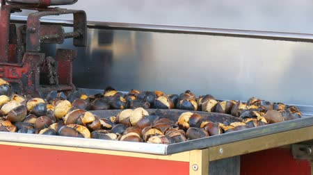 fogueira : male salesman is cooking Roasted chestnuts on a city street. Street food, the hot cooked chestnuts Vídeos