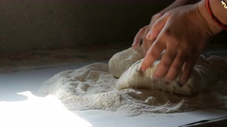 pasta maken : Female hands knead the dough at the home vintage kitchen in the village. A ray of sun falls on the dough and flour flying in air. Homemade baking