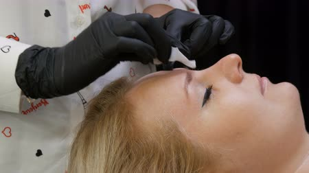 microblading : Beautician makes eyebrow correction to his patient. Degreasing the skin before procedure with a special alcohol wipe