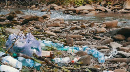 tényező : Mountain fast clean stream, on rocky shore, which has garbage, plastic bottles, bags. The human factor in environmental pollution. Special garbage defocus