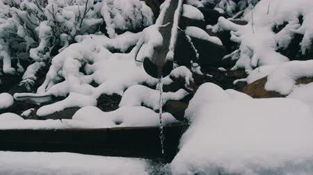 extreme weather : Heavy snow clean, transparent mountain water stream that flows down wooden gutter into special trough