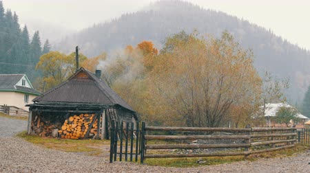 tlen : Ukraine, the highest mountain village of Carpathians, Dzembronya. The first snow in October. A wooden house is heated with firewood. Smoke comes from chimney