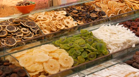 citrom és narancsfélék : A variety of dried fruits on the counter of Turkish store. Dried oranges, lemons, kiwi, pineapple, apricots, dates Stock mozgókép