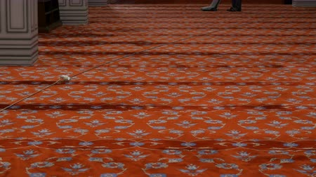 vácuo : Man vacuuming huge red carpet in a blue mosque, Istanbul