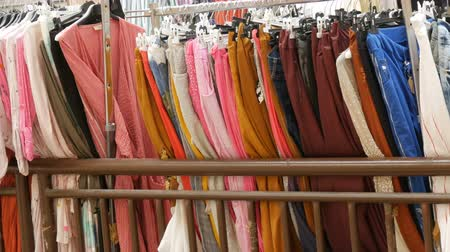 разница : Various womens clothes hanging in row on hangers in a clothing store