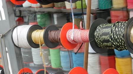 nejlon : Strong ropes of different colors are wound on special reels on the counter in store Stock mozgókép