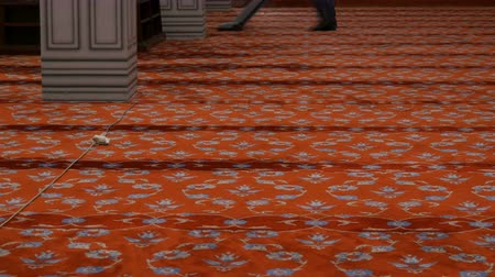 arrumado : A large gray vacuum cleaner cleans the carpet. Man vacuuming a huge red carpet in blue mosque, Istanbul