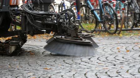 münchen : Cleaning Machine brush removing yellow fallen leaves from the autumn street. Cleaning leaves in fall. Asphalt machine cleaning in Germany, Munich