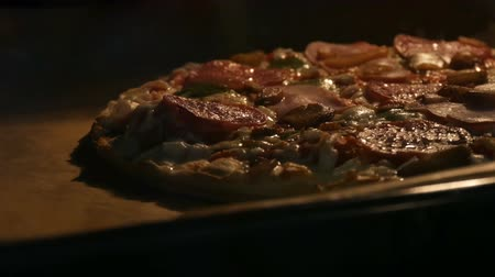 étkező : Delicious pizza with mushrooms, salami, bacon, herbs, and cheese is cooked in oven