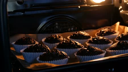 pastelaria : Delicious chocolate muffins are cooked in the oven. Chocolate muffins in paper molds sprinkled with chocolate powder in form of cubes