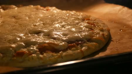 diner : Delicious pizza richly strewn with cheese is cooked in the oven. Cheese on pizza melts from oven heat close up view Stock Footage